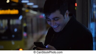 Using a Phone While Waiting for the Train - A man is happily...