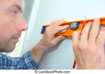 Using a spirit level to check a wall is straight