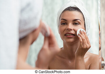 Using a toner - Young woman is using a toner for her...