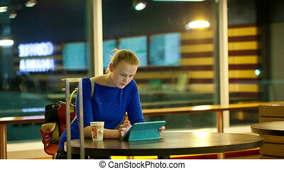 Young woman having coffee and using a tablet PC in the airport terminal