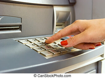 Using bank ATM - Woman\'s hand dialing pin on bank ATM...