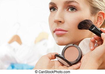 Using blush brush to apply blush on cheeks