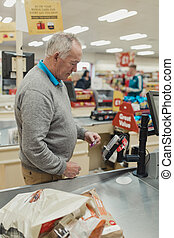 Using Contactless at the Supermarket - Senior man making a...