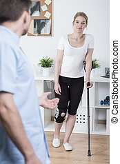 Using crutch after knee injury - Young woman using crutch...