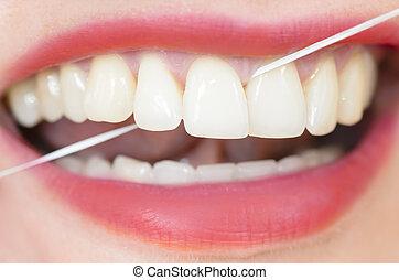 Using Dental Floss - Woman using dental floss