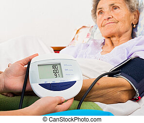 Using Digital Blood Pressure Gauge - Home care nurse using...