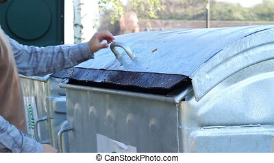 Using Dumpster - A man is throwing garbage to the public...