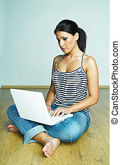 Using laptop computer - Young pretty women on wooden floor...