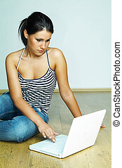 Using laptop computer - Young pretty women on wooden floor ...