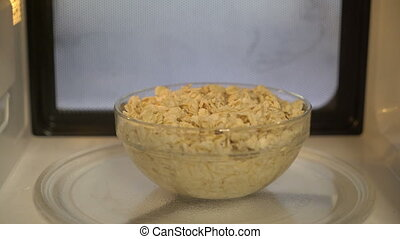 Using microwave for cooking and heating food. Bowl of...