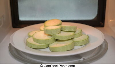 Using microwave for cooking vegetables. Raw sliced zucchini...