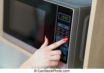 Using microwave oven - Detail of female hand while using the...