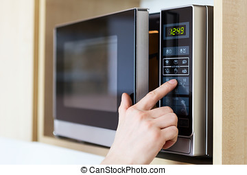 Using microwave oven - Detail of male hand while using the...