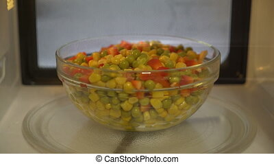 Using microwave to heat up food. Cooking warm vegetable...