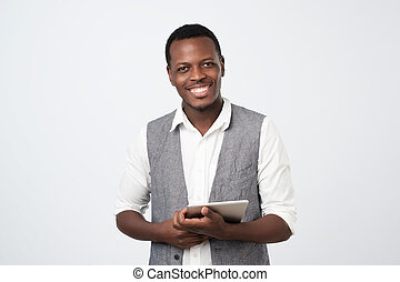 Handsome young african man in shirt and vest with digital tablet and smiling