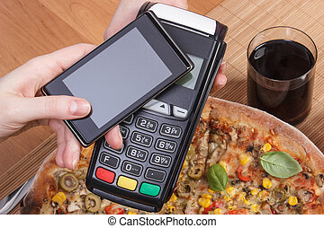 Using payment terminal and mobile phone with NFC technology for paying in restaurant