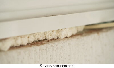 Using polyurethane foam to fill gaps during installing a window.