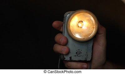 Using Retro Flashlight - In a dark room, someone is turning...