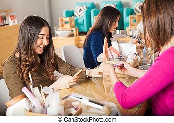 Using smartphone at a nail salon
