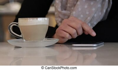 Using smartphone on coffeshop table