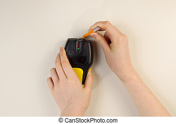 Using Stud Finder on interior home wall - Photo of female...