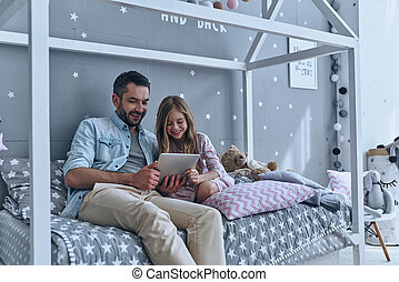 Using technologies for fun. Young father and his little...