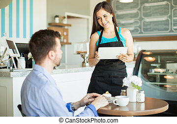 Using technology for work in a cafe - Attractive young...