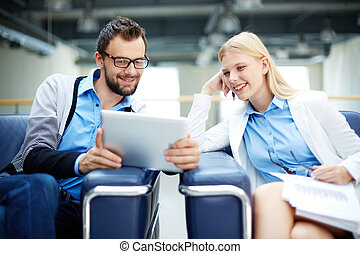 Using touchpad - Two business people discussing document or...