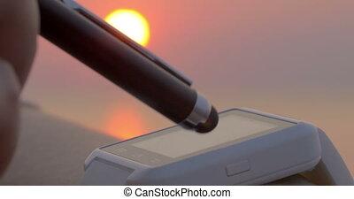 Using touchscreen smartwatch at sunset