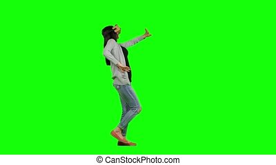 Virtual reality game, girl with pleasure uses head-mounted display, woman in a virtual reality mask looks around, manipulates his surroundings. and walking, with a virtual reality head set, on green screen