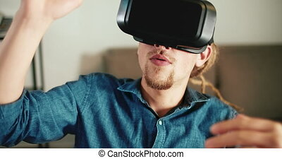 Using Virtual Reality - Young man with dreads hair dressed...