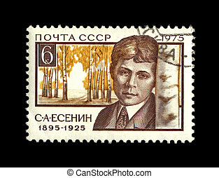 USSR - CIRCA 1975: cancelled stamp printed in the USSR, shows famous russian  poet Sergey Esenin and birch trees as background, circa 1975. vintage post stamp on black background.