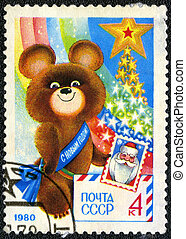 USSR - CIRCA 1979: A stamp printed in USSR shows Olympic Bear Holding Stamp - a symbol of the Moscow Olympics games, New Year 1980, circa 1979