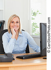 ute blonde woman with chin on hand behind a desk looking at screen in an office