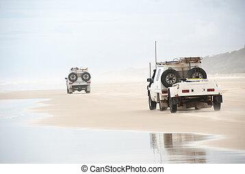 Ute trucks beach driving on tropical fraser island,...