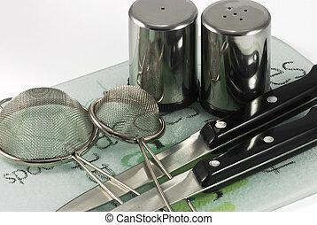 Utensils on ceramic tiles - Kitchen utensils of stainless...
