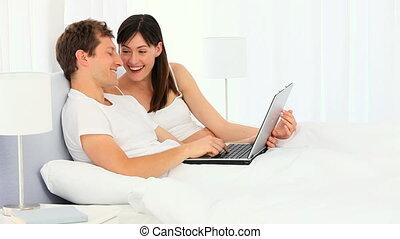 utilisation, couple, ordinateur portable, jeune, heureux