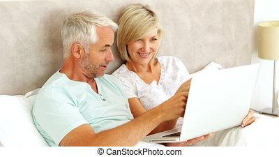 utilisation, couple, ordinateur portable, lit, bavarder