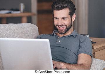 utilisation, séance, beau, maison, homme, divan, sien, sourire, gai, ordinateur portable, quoique, blogger., jeune