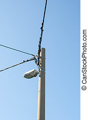 Utility pole with wires against a clear blue sky.