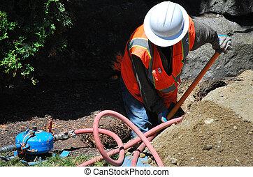 Utility repairman. - Utility repairman fixing a broken water...
