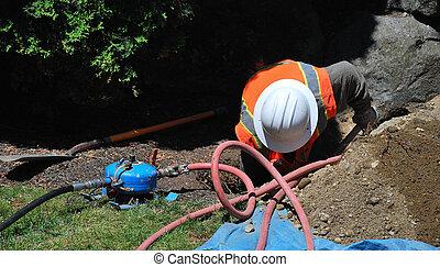 Utility worker. - Utility worker repairing a broken water ...