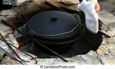 Uzbek national dish pilaf in a large cast-iron cauldron on...