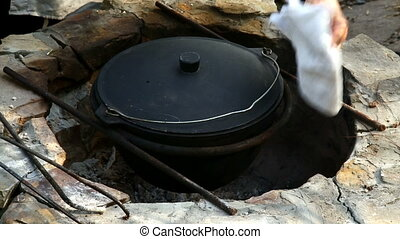 Uzbek national dish pilaf in a large cast-iron cauldron on the fire. Mixed ready pilaf