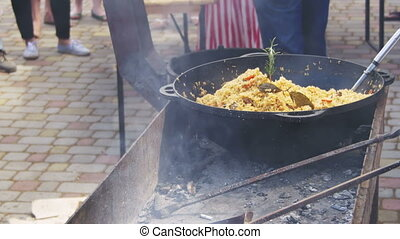 Uzbek Pilaf is Cooked in a Cauldron over a Fire on Street