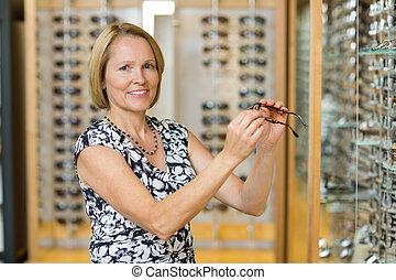 válogat, nő, látszerész, bolt, szemüveg