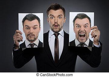 välja, maskera, på, today., snopen, ung man, in, formalwear, holdingen, två, fotografier, av, sig själv, expessing, olik, sinnesrörelser, medan, isolerat, på, grå