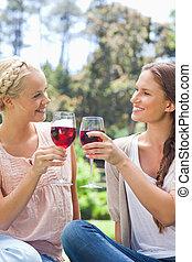 vänner, klirrande, deras, vin glasögon, le