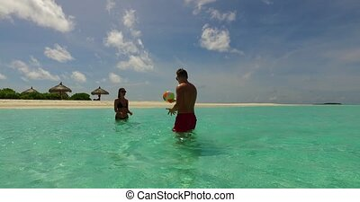 v14852 two 2 people playing ball romantic young couple on a tropical island of white sand beach and blue sky and sea