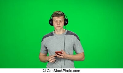 va, grand, écouteurs, texting, homme, écran, smartphone, vert, studio.
